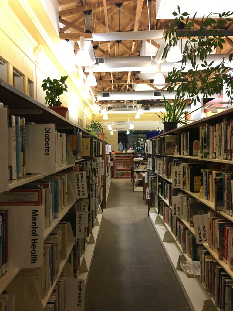 Image of a library aisle shows the very high ceilings, open rafters, and plants on tops of shelves