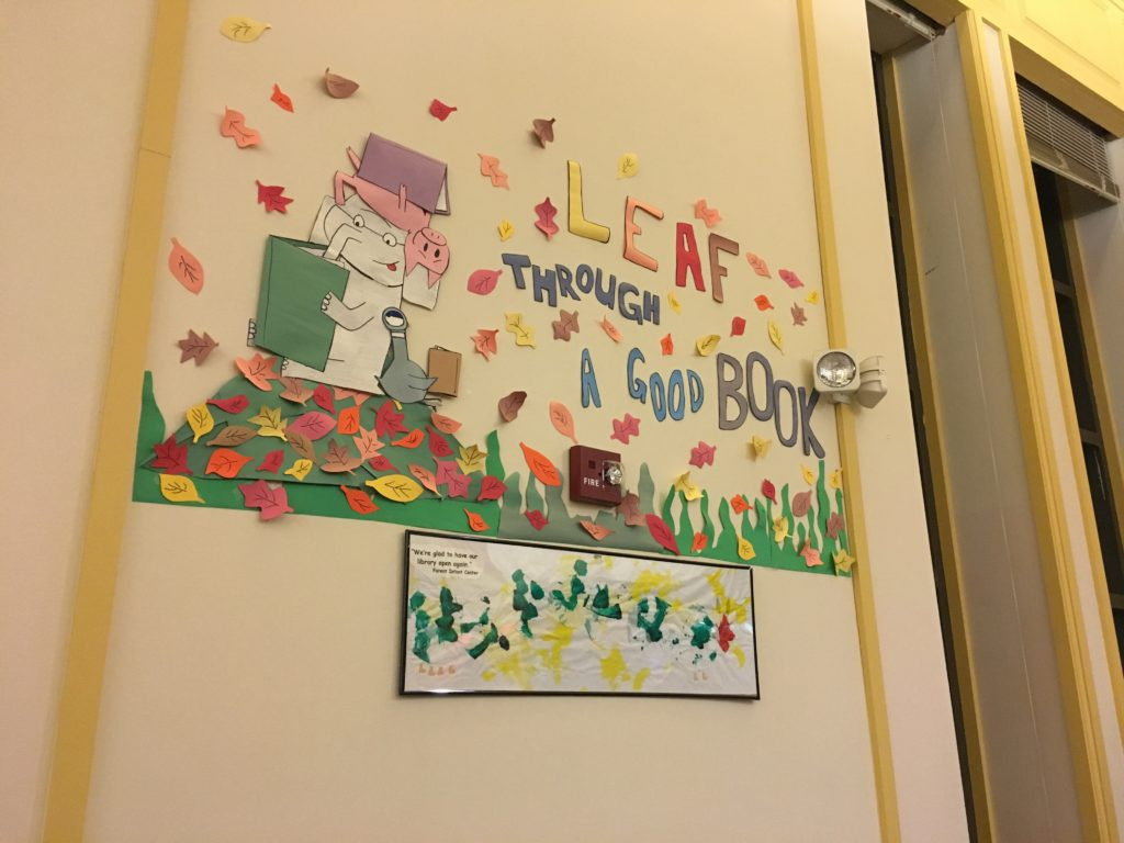 "Paper wall decoration featuring falling leaves surrounding an elephant, a pig, and a goose who are all reading, with the text ""leaf through a good book"""