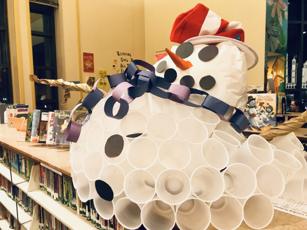 A round snowman made of plastic cups, wearing a paper chain scarf and a striped hat