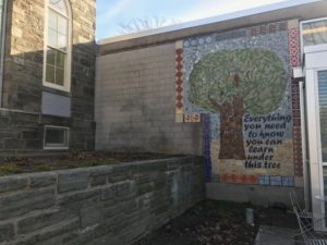 "Mosaic on library with image of tree and the phrase ""Everything you need to know you can learn under this tree"""
