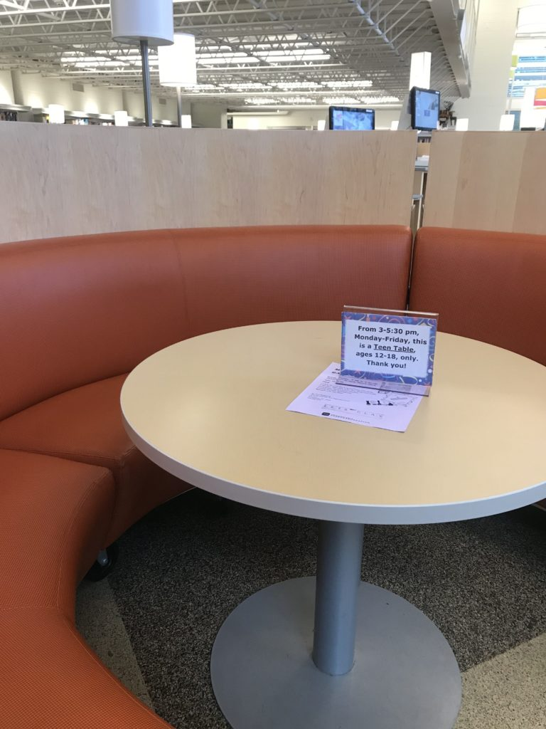 Round booth with sign for times for teen-only seating