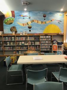 "Table and chairs in front of bookshelves. Above the bookshelves, there is a brightly colored mural with a blue background and images of hot air balloons and the sun, plus the phrase ""The sky's the limit."""