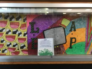 "Display case with vibrant artwork including the word ""LEAP"", and a sign about the LEAP program in the foreground"